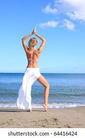 Fashion shot of a beautiful woman in a bikini on the beach