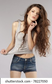 fashion shot of beautiful young woman with long curly hair in casual dress