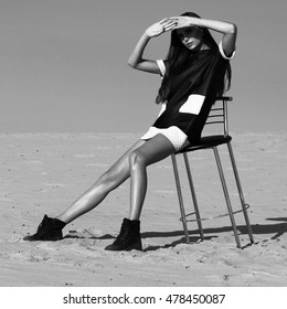 Fashion shot in the desert. A beautiful sexy girl in a black dress. The girl in the desert in fashionable clothes for advertising.