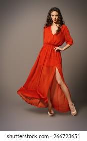 Fashion shot of the elegant woman in beautiful long dress posing in motion. Studio shot.