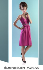 fashion shot of an elegant young woman posing on turquoise background wearing a pink evening dress and a fashion up-do