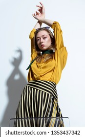 Fashion shot, girl model on the background of a white wall in the studio.