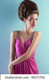 fashion shot of a gorgeous brunette with a a fashion hair up-do and wearing an elegant pink evening dress with small pearls