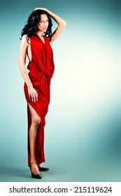 Fashion shot of a gorgeous brunette woman in elegant red dress. Full length.