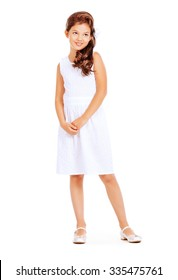 Fashion shot of a pretty eight-year girl wearing white dress. Studio shot. Kid's beauty, fashion. Isolated over white.