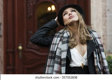 fashion shot of pretty young woman near e old fashion door , she is looking up to the sky , wearing scarf and hat . freckles on face
