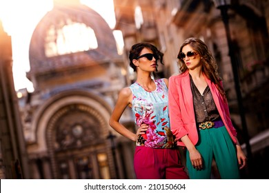 Fashion shot of two elegant beautiful girls in the sunset wearing sunglasses. Two young women outdoor on the street. Shopping inspiration