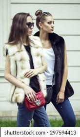 Fashion shot of two elegant beautiful girls in the sunset wearing sunglasses, fur vests . Two young women outdoor on the street. Shopping inspiration