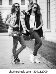 Fashion shot of two elegant beautiful girls in the sunset wearing sunglasses, fur vests . Two young women outdoor on the street. Shopping inspiration. Monochrome (black and white)  photo