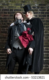 Fashion shot of woman  dressed as Jack the Ripper stealing man's handkerchief.