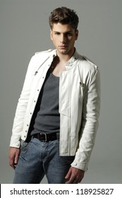 Fashion Shot of a young man in whit jacket on light background