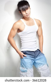 Fashion shot of a young and muscular Chinese male model wearing singlet and beachwear bermudas. Photographed in studio with interesting shadows on wall