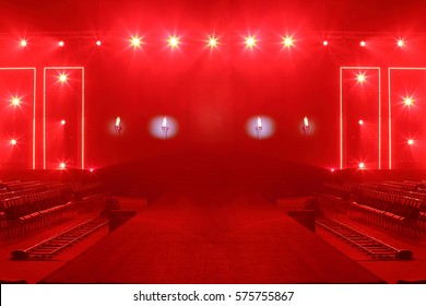 Fashion Show Catwalk Runway Stage in Reddish atmosphere with smoke, spotlight par lighting in red color over hanging construction with black walk way and vdo camera dolly with empty seat, copy space