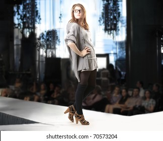 Fashion show with redhead fashion model posing in high hills black tights gray skirt and shirt over