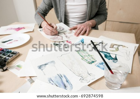 Fashion sketches on designer desk with unrecognizable man in the background