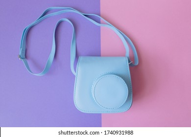 Women's fashion sky blue turquoise instax camera bag on purple and pink background . Spring summer collection fashion concept. View from above . Flat lay. Fashion accessories on pink and purple bright