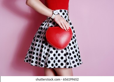 Fashion small heart shape red bag in hand of girl . White and black polka dots skirt