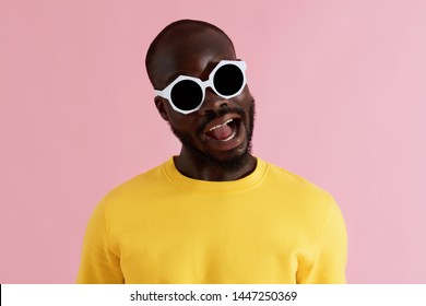Fashion. Smiling black man in sunglasses and yellow clothes on pink background colorful portrait. Happy young african american male model in stylish glasses and sweatshirt laughing in studio