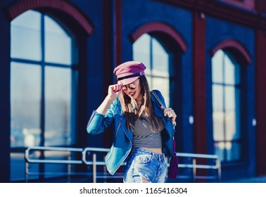 fashion smiling model in hat wearing sunglasses and posing outdoor. Jeans, leather, hat, jacket.