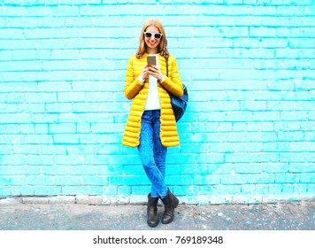 Fashion smiling woman with a smartphone on blue brick background in the city