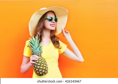 Fashion smiling woman in sunglasses and hat with pineapple over colorful orange background