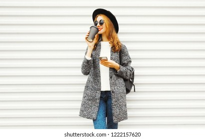 Fashion smiling woman using smartphone with coffee cup on white wall background