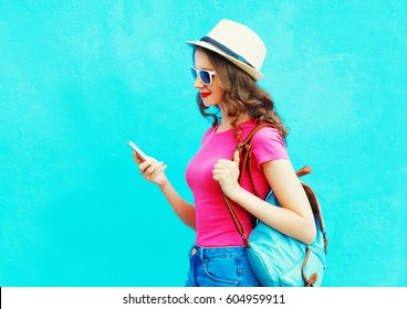 Fashion smiling woman using smartphone wearing straw hat and backpack over colorful blue background, profile view