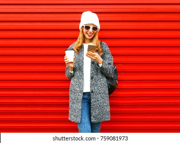 Fashion smiling woman is using smartphone with coffee cup on a red background in the city