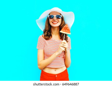 Fashion smiling young woman is holding a slice of watermelon in the form of ice cream a colorful blue background