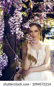 fashion spring outdoor portrait of beautiful young woman bride  in luxurious wedding dress and diadema posing among flowering wisteria trees in sunny garden