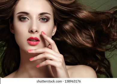 Fashion spring/summer look. Beautiful young woman with bright makeup, clean face, flying healthy long hair, pink manicure.