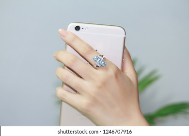 Fashion sterling silver ring with blue topaz gemstone on female's finger, holding smartphone