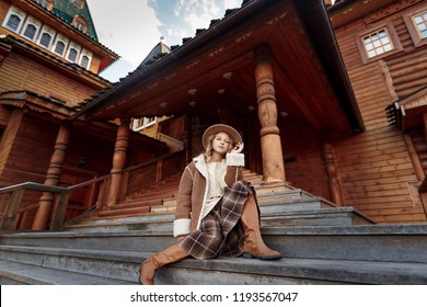 fashion story. blonde girl in the park at the wooden house