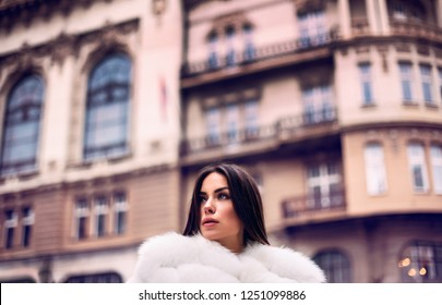 Fashion street closeup portrait of young stylish beautiful sensual woman in elegant clothes and luxurious fur coat. Outdoor photo.