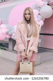 fashion street look of beautiful young woman with long blond hair in elegant clothes walking by the street