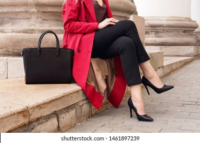Fashion street portrait woman wear trendy red trench coat, heels, holding big bag, sitting on stairs.