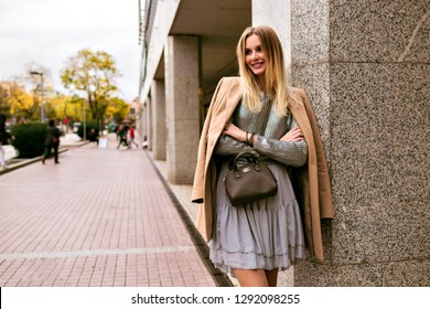 Fashion street style picture of blonde elegant woman, wearing luxury silk dress, trendy sweater, cashmere coat and leather bag, soft warm colors, spring autumn mid season mood.