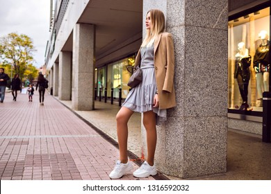 Fashion street style portrait of young woman wearing modern glamour outfit, light silk dress and ugly sneakers, cashmere classic beige coat and crossbody bag. Europe city, posing near shopping mall