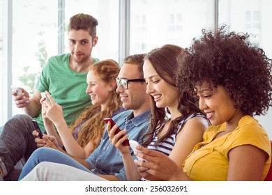 Fashion students looking at their smartphone at the college
