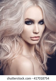 Fashion studio photo of beautiful blonde woman with smoky eyes makeup