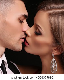 fashion studio photo of beautiful couple in elegant clothes, gorgeous woman with long blond hair kissing handsome brunette man