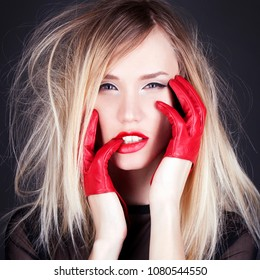 Fashion studio photo of beautiful girl with red gloves and red lips. Blond Young Woman
