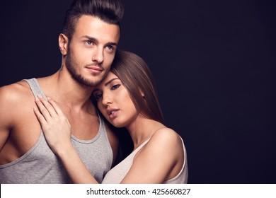 Fashion studio photo of beautiful handsome couple in love.Studio fashion portrait. Toned photo.