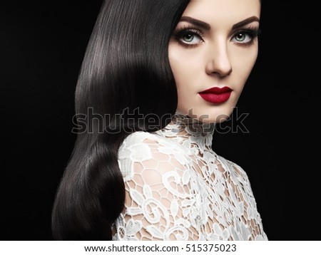 Fashion studio photo of beautiful model girl brunette with long curled hair and red lips. Hairstyle Hollywood wave. Wedding image hairstyle. Perfect make up