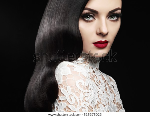 Fashion Studio Foto von schönen Mädchen-Brunette mit langen gekuppelten Haaren und roten Lippen. Hollywood-Hairstyle-Welle. Hochzeitsbild-Frisur. Perfekte Make-up