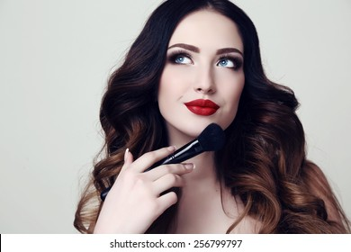 fashion studio photo of beautiful sensual woman with dark hair and bright makeup, holding makeup brush in hand