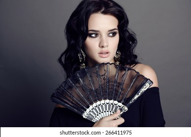 fashion studio photo of beautiful sensual woman with dark hair and bright makeup holding black lace fan in hand