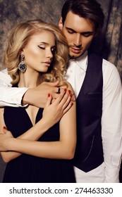 fashion studio photo of beautiful sensual couple in elegant clothes