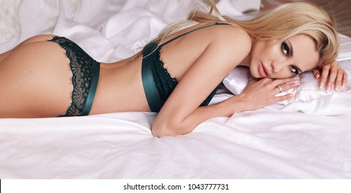 fashion studio photo of beautiful sexy woman with long blond hair and evening makeup in elegant lingerie