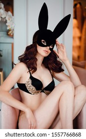 fashion studio photo of beautiful sexy woman with dark hair in luxurious lingerie and leather bunny mask